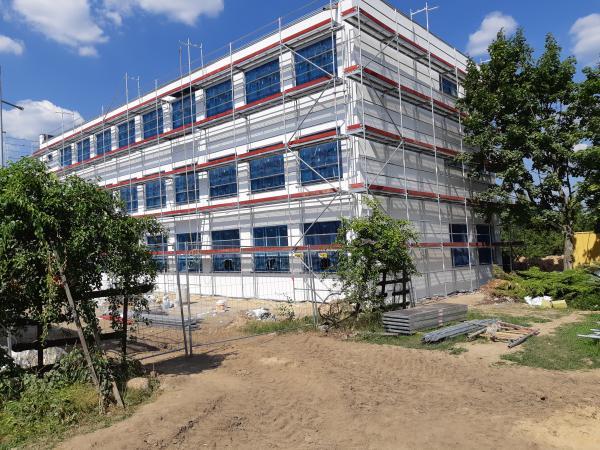 Budynek szkoły z zewnątrz zamontowane nowe okna w trakcie prac elewacyjnych- kliknij aby powiększyć